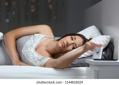 Tired woman on a bed waking up in the night turning off alarm clock