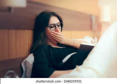 Tired Woman Reading Book in Bed before Sleep. Sleepy girl trying to finish a boring novel