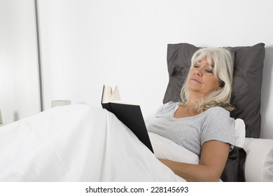 Tired woman reading a book in bed