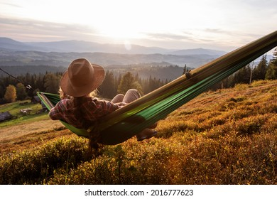 tired woman resting after climbing in a hammock at sunset - Shutterstock ID 2016777623