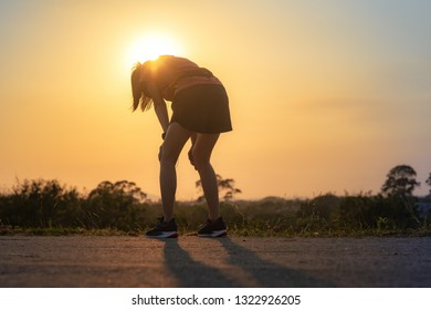 tired woman runner taking a rest after running hard on countryside road
