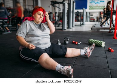 Tired woman sits on the floor in gym