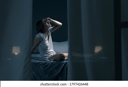 Tired woman sitting in bed at night with open window, she is suffering from the heat and she is unable to sleep