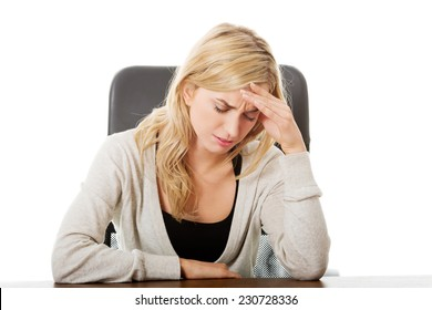 Tired woman sitting at the desk touching head.