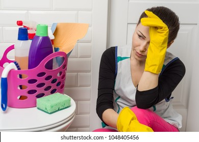 Tired woman sitting on bathroom floor with cleaning supplies and equipment
