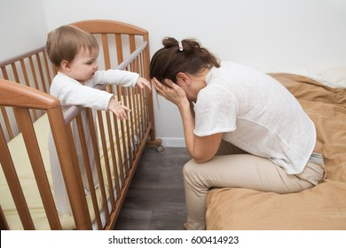 tired woman sitting on the bed near children's cot.