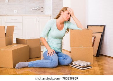 Tired woman sitting on the floor while moving into new home.