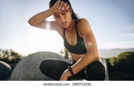 Tired woman sitting and resting after workout. Woman feeling exhausted after training session wiping her sweat from her forehead.