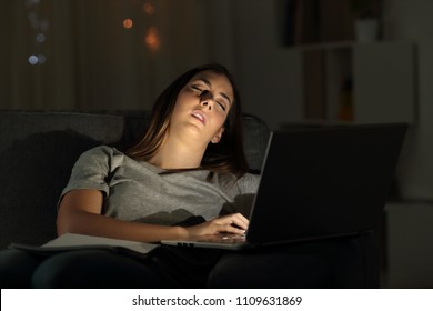 Tired woman sleeping on a couch beside a laptop in the night at home