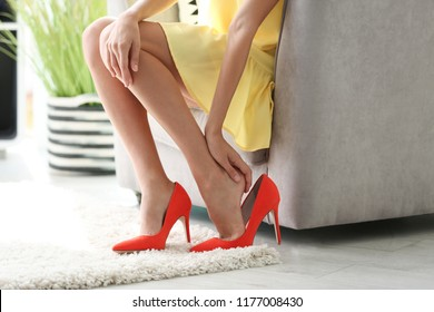 Tired woman taking off shoes at home, closeup view