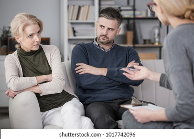 Tired woman talking to a mediator about her bad relationships with her husband, who is quarrelsome