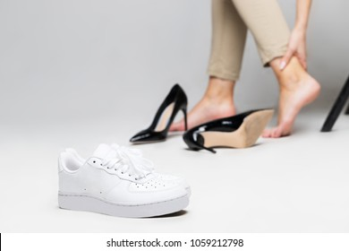 Tired woman touching her ankle, suffering from leg pain because of uncomfortable shoes, feet pain wear high heel shoes after walk, focus on comfortable sneakers.Comfortable and uncomfortable shoes