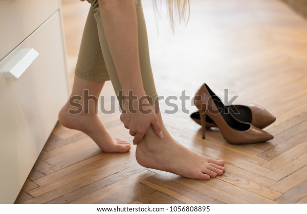 Tired woman touching her ankle, suffering from leg pain because of uncomfortable shoes, feet pain wear high heel shoes after work or walk, selective focus .Swelling of feet in shoes.Foot fatigue