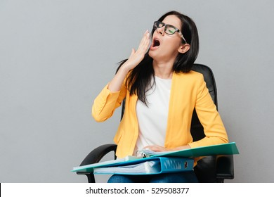 Tired woman wearing eyeglasses and dressed in yellow jacket holding folders while yawning and sitting on office chair over grey background. Eyes closed.