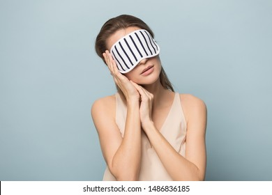 Tired woman wearing sleeping mask isolated on blue studio background relax fall asleep on hands, exhausted calm female in cozy homewear rest sleep standing, dream seeing sweet dreams