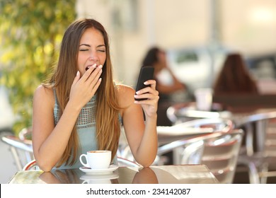 Tired woman yawning while is working on the phone at breakfast in a restaurant