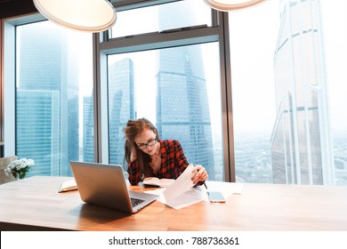 Tired of work - young beautiful woman in glasses and casual clothes - accountant of large company - looking at charts and reports working sitting at table with computer on background of large window