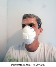 Tired worker after sanding wall wearing mask.