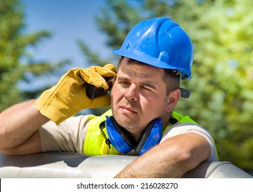 Tired worker with walkie talkie and safety equipment on oil plant