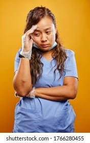 tired and worn down filipina nurse portrait on orange background