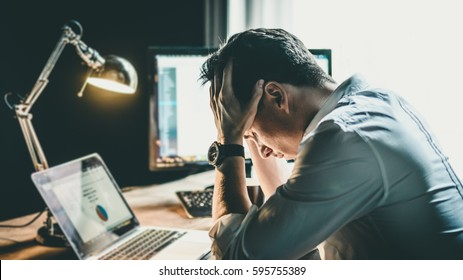 Tired and worried business man at workplace in office holding his head on hands after late night work, concept
