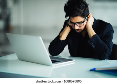 Tired and worried indian business man at workplace in office