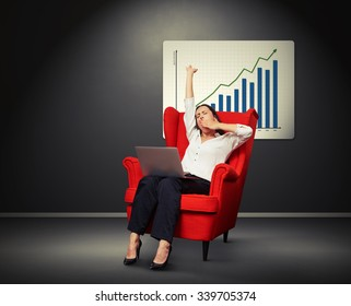 tired yawning businesswoman sitting with laptop on chair against placard with positive graph on the wall on dark room