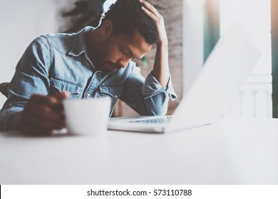 Tired young African man using laptop while sitting at the table on a sunny morning.Concept of people working hard home.Blurred background,flare effect
