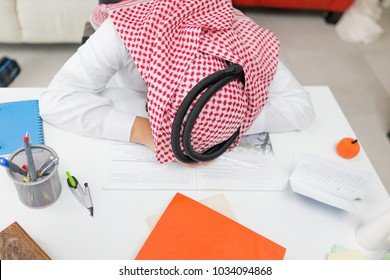 Tired Young Arab Boy Working on Laptop on Desk
