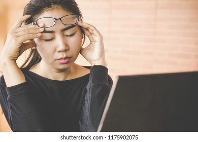 tired young Asian business woman having eye pain ,headache and dizzy from working hard on computer screen