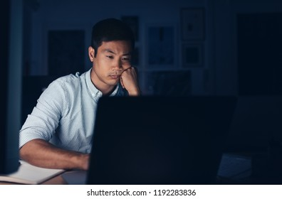 Tired young Asian businessman sitting at his desk working on a laptop in a dark office late in the evening