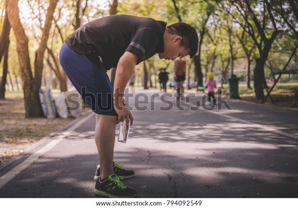 a tired young Asian male resting holding a bottle of drinking water in the road at the park after a daily exercise, running jogging for his fitness in the warm summer morning