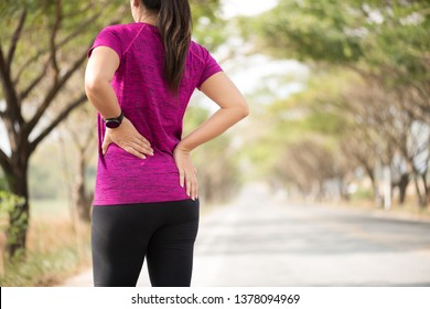 Tired Young asian Sport girl feel pain on her back and hip while exercising, health care concept.