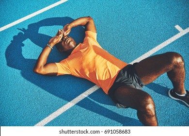Tired young athletic African man in sportswear lying on the lanes of a running track taking a break from training