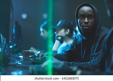 Tired young Black app developer in hoodie sitting at table and advising colleague while working on new app