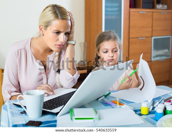 Tired young blonde woman irritated as her preschooler daughter diverts her from work at home