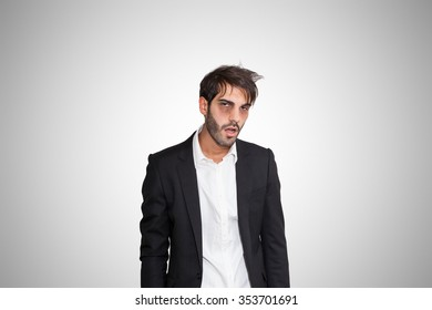 Tired young business man with dark eye bags, on gray background.
