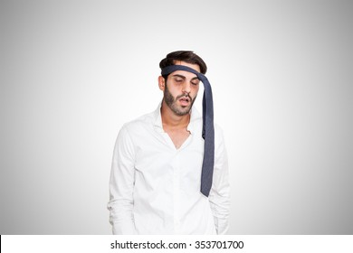 Tired young business man with dark eye bags and tie on head, on gray background.