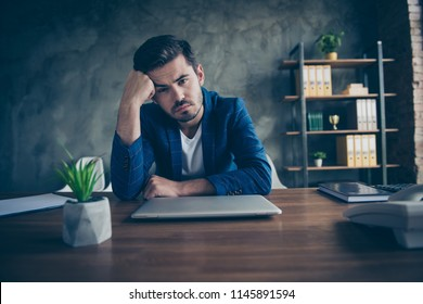 Tired young businessman with a beard laid his head on his fist and looks directly into the camera