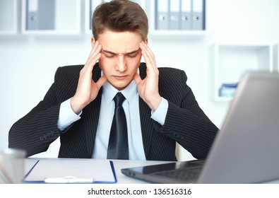 Tired young businessman with problems and stress at his workplace in bright office