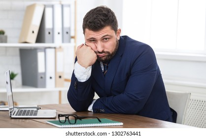 Tired young businessman sitting on workplace and looking at camera