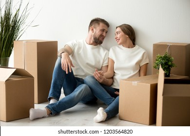 Tired young couple sitting leaning back against wall looking at each other in new apartment, packaged belongings in cardboard boxes, family just arrived in house, man and woman beginning live together