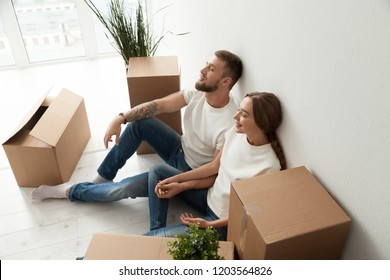 Tired young couple sitting leaning back against wall with closed eyes in new apartment with packaged belongings in cardboard boxes, family just arrived in house, man and woman beginning live together