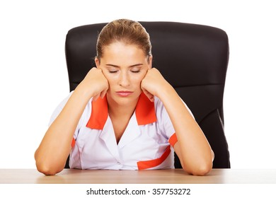 Tired young female doctoror nurse sitting behind the desk.