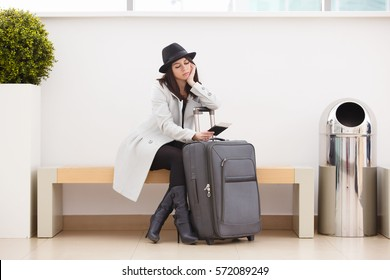 Tired young hipster traveler women in coat and black hat waiting at airport. Young girl with suitcase sitting and depressed because the flight is delayed