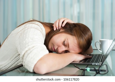 A tired young lady sitting in front of her laptop while sleeping.