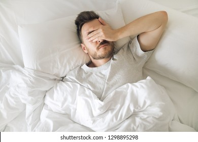 Tired young man in bed closing his eyes before waking up. Hangover morning. Sleep disorder and problems.