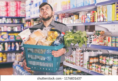 Tired young man with heavy shopping basket filled food products in supermarket