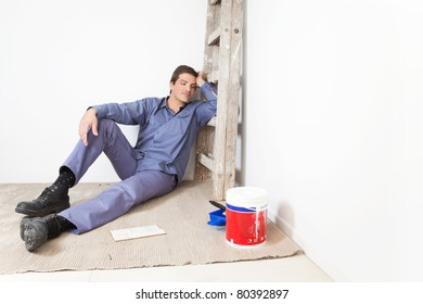 Tired young man leaning on ladder and sleeping