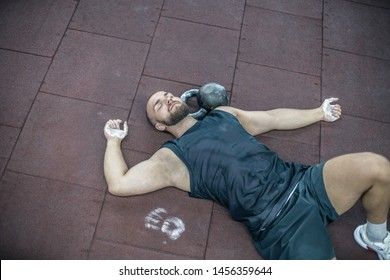 Tired young man lying on floor and relaxing in gym after training. Male relaxing after workout session at gym